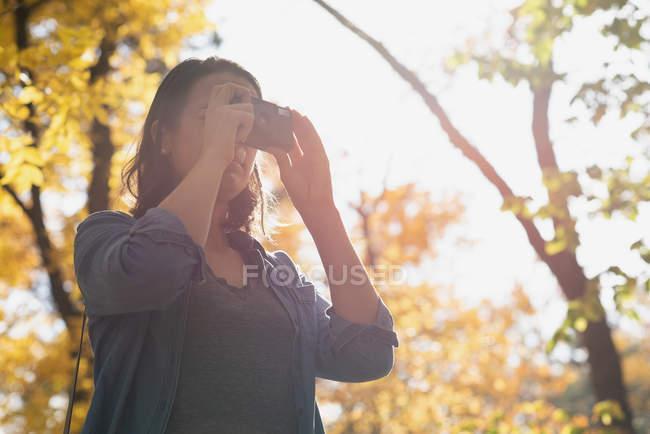 Женщина щёлкает фотографиями с камерой в солнечный день — стоковое фото