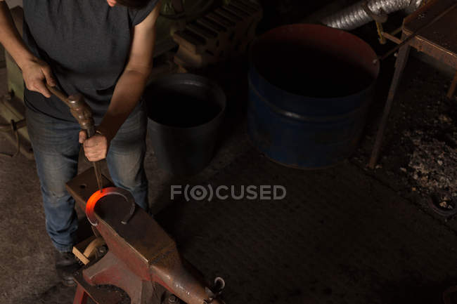 Low section of female metalsmith molding horseshoe in factory — Stock Photo