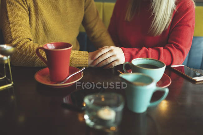 Mid section of couple holding hands in cafe — Stock Photo