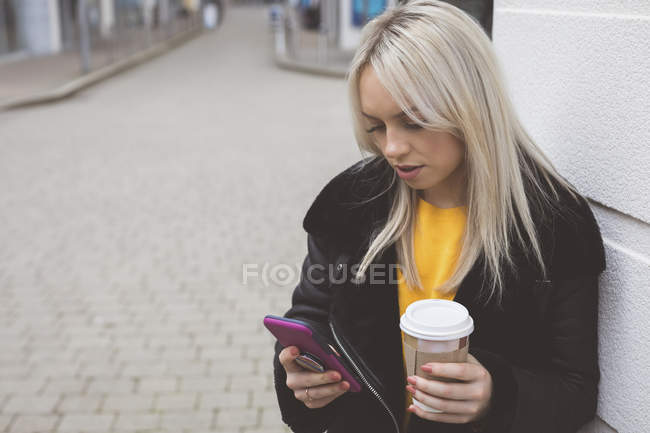 Beautiful woman using mobile phone while having coffee — Stock Photo