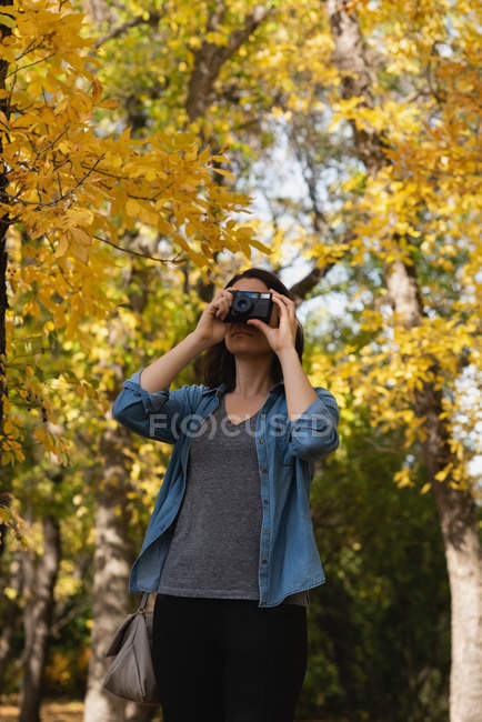 Woman clicking photos with camera on a sunny day — Stock Photo