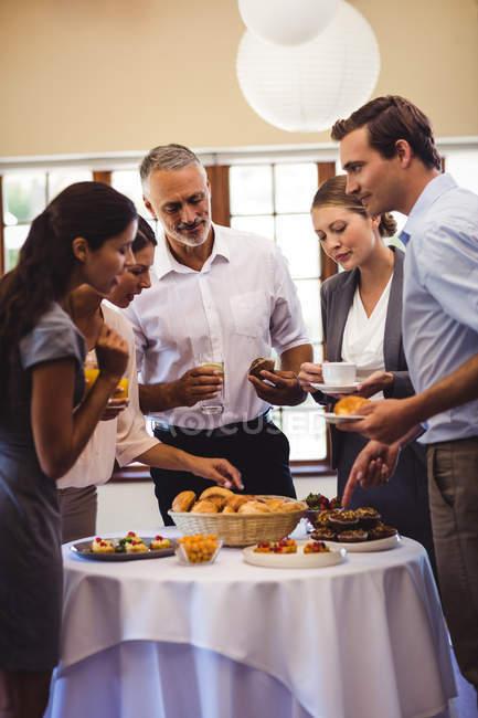 Business people having dessert on table in restaurant — Stock Photo