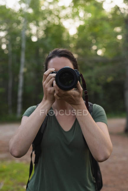 Close-up of woman clicking photos with camera in forest — Stock Photo