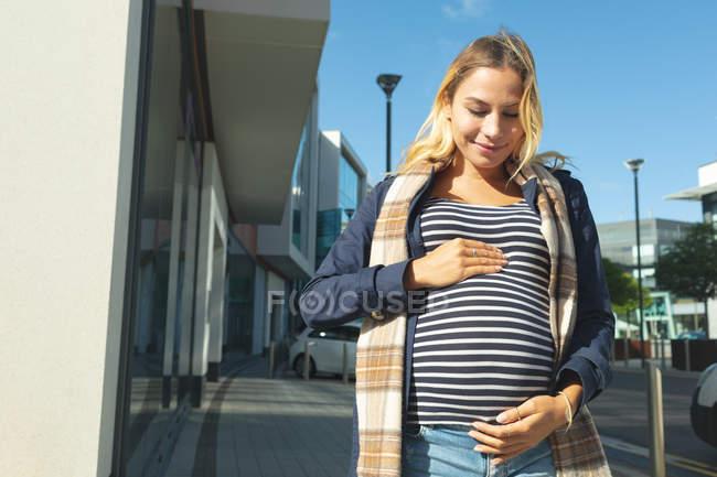 Беременная женщина трогает свой живот в городе в солнечный день — стоковое фото