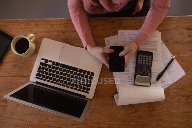 Media sezione di donna che utilizza il telefono cellulare a casa — Foto stock