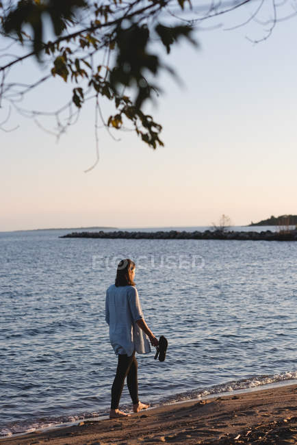 Woman walking at the beach on a sunny day — Stock Photo