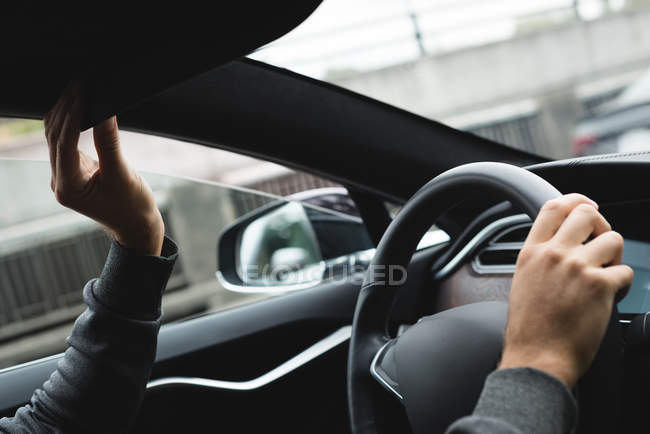 Close-up of man adjusting rear view mirror while driving a car — Stock Photo