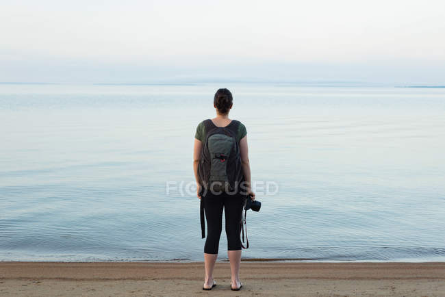 Rear view of woman standing with backpack and camera on the beach — Stock Photo