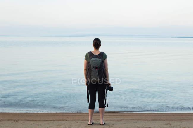 Visão traseira da mulher de pé com mochila e câmera na praia — Fotografia de Stock