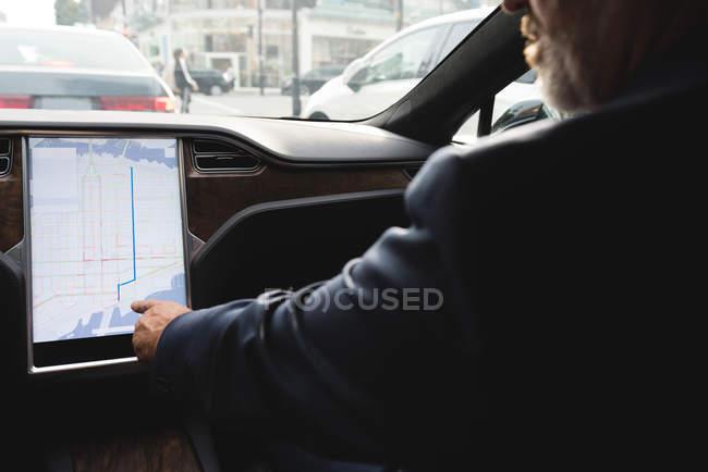 Section médiane de l'homme d'affaires en utilisant navigator carte pendant que vous conduisez une voiture — Photo de stock