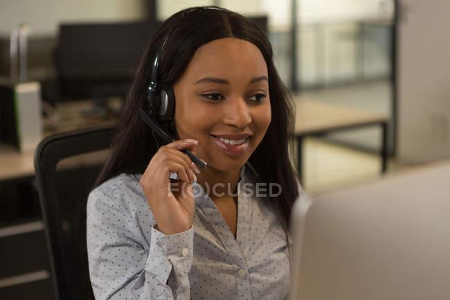 Ejecutivos de servicio al cliente hablando por el auricular en la oficina - foto de stock