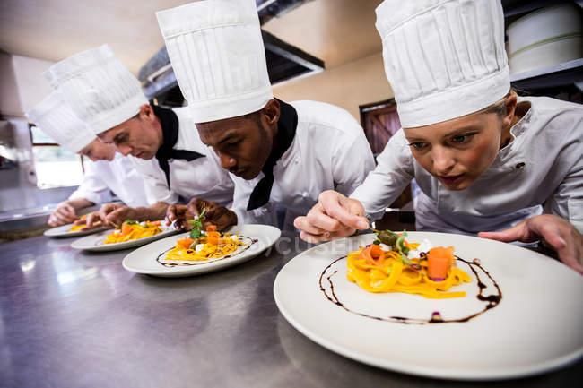 Grupo de chef guarnición de alimentos en platos - foto de stock