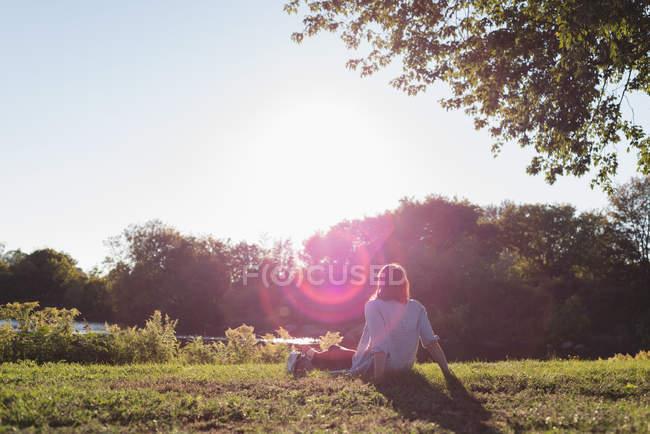 Rear view of woman relaxing near riverside — Stock Photo