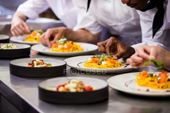 Close-up of chef garnishing food on plates — Stock Photo