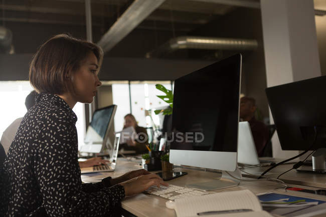 Female executive working at desktop in office — Stock Photo