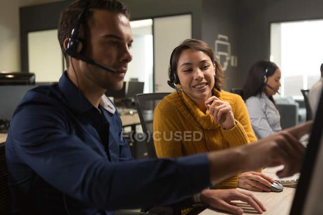 Ejecutivos de servicio al cliente discutiendo sobre pc de sobremesa en la oficina - foto de stock