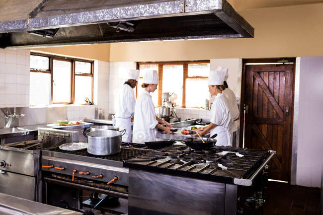 Groupe de chef travaillant en cuisine au restaurant — Photo de stock