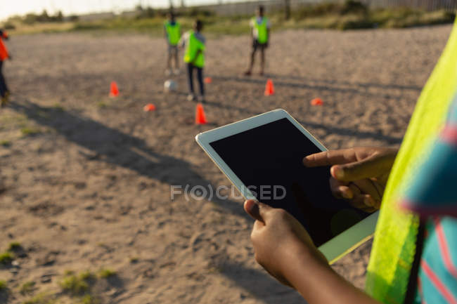 Mid section of kid using digital tablet in the ground — Stock Photo