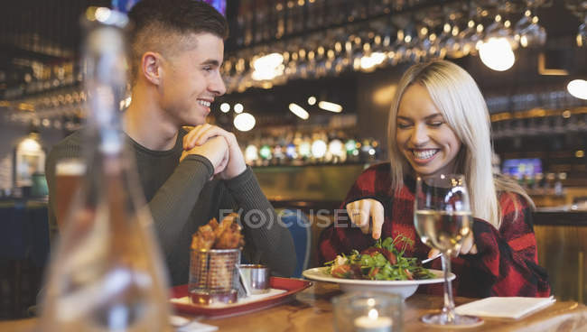 Happy couple having food in restaurant — Stock Photo