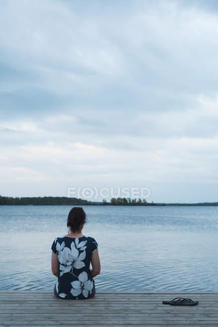 Vista posteriore della donna seduta sul molo — Foto stock