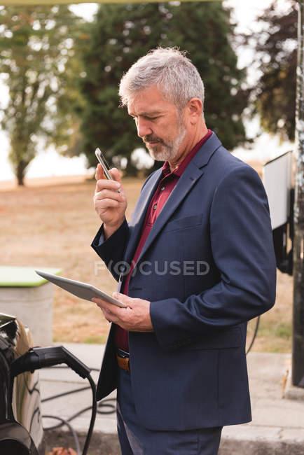 Geschäftsmann benutzt digitales Tablet beim Telefonieren an der Ladestation — Stockfoto