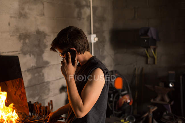Young female metalsmith talking on mobile phone while working in factory — Stock Photo