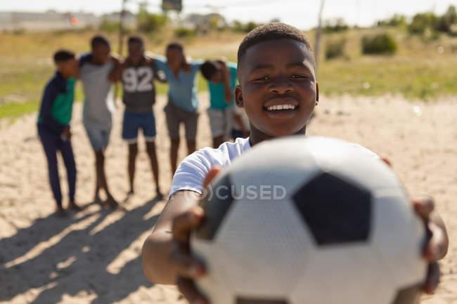 Мальчик держит футбол в земле в солнечный день — стоковое фото