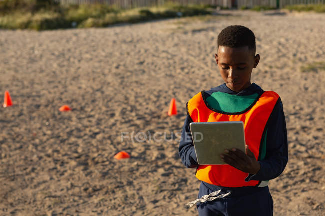 Kid using digital tablet in the ground on a sunny day — Stock Photo