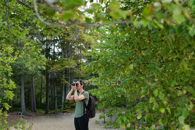 Donna cliccando foto con macchina fotografica nella foresta — Foto stock