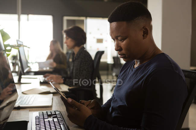 Executive using digital tablet at desk in office — Stock Photo