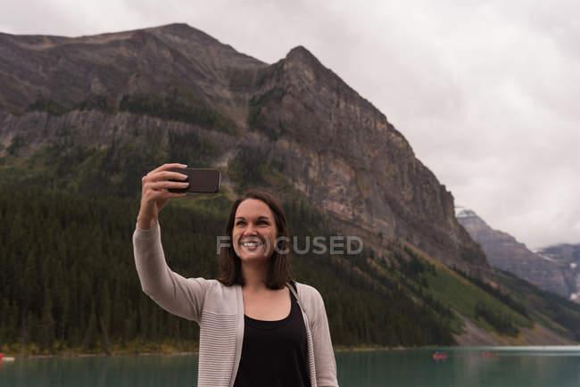 Mujer feliz tomando selfie con teléfono móvil cerca de la orilla del lago - foto de stock