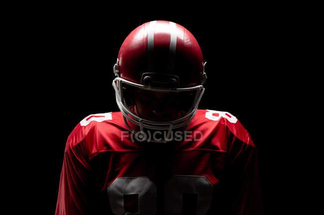 Американский футболист, стоящий в регби-шлеме на черном фоне — стоковое фото