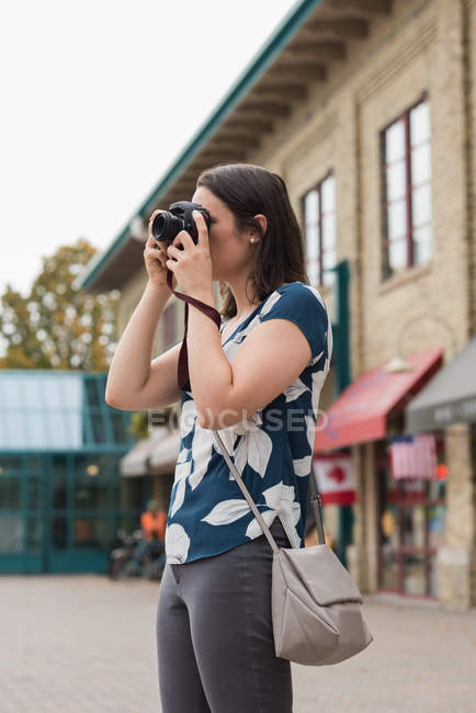 Beautiful woman clicking photos with camera in the city — Stock Photo