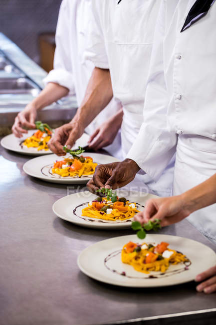 Mid section of chef garnishing food on plates — Stock Photo