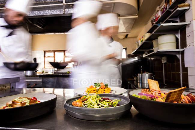 Nahaufnahme von Lebensmitteln auf einen Teller und Köche des Hintergrunds — Stockfoto