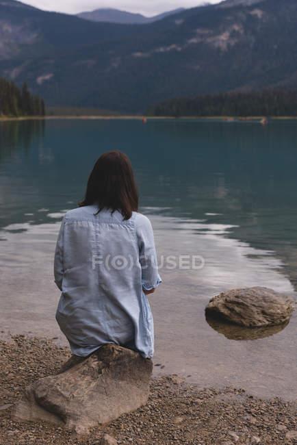 Rückansicht einer Frau, die am Seeufer sitzt — Stockfoto