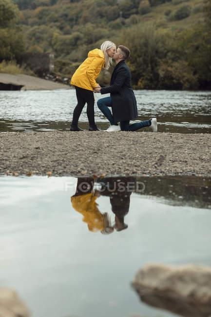 Vista lateral de la romántica pareja besándose cerca de río - foto de stock