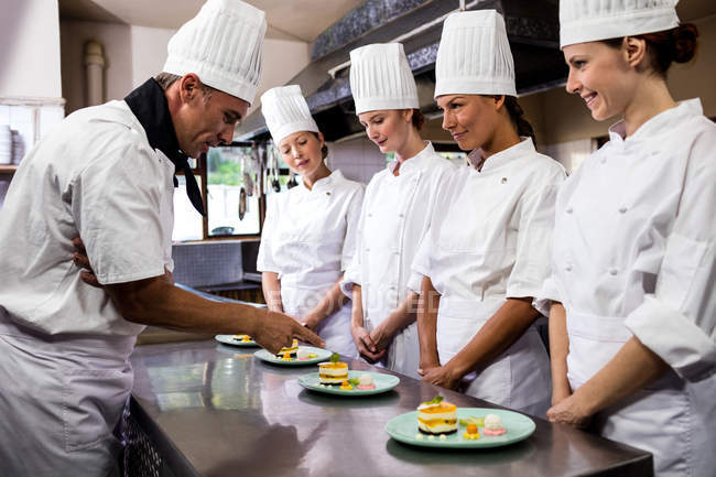 Head chef inspecting dessert plates in restaurant — Stock Photo