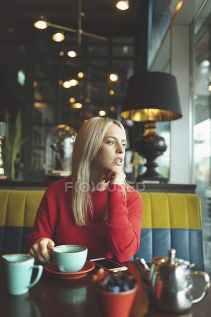 Nachdenkliche Frau in Cafeteria wegschauen — Stockfoto