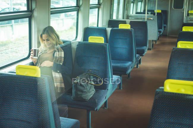 Mujer embarazada tocándose el vientre mientras viaja en tren - foto de stock