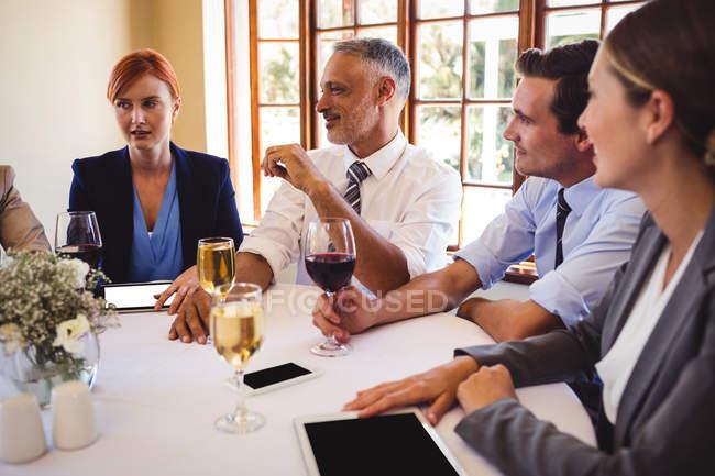 Деловых людей, взаимодействующих друг с другом на стол в ресторане — стоковое фото