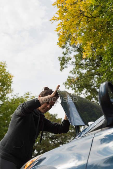 Mulher verificando um carro durante o colapso em um dia ensolarado — Fotografia de Stock