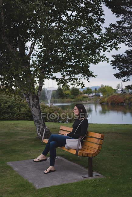 Thoughtful woman sitting on bench near riverside — Stock Photo