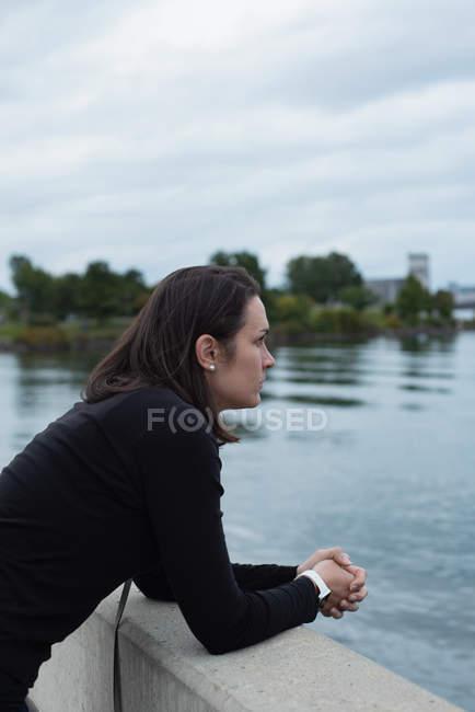 Продуманий жінка, стоячи біля річки — стокове фото