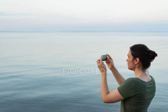 Вид збоку жінки, натиснувши фотографій за допомогою мобільного телефону — стокове фото