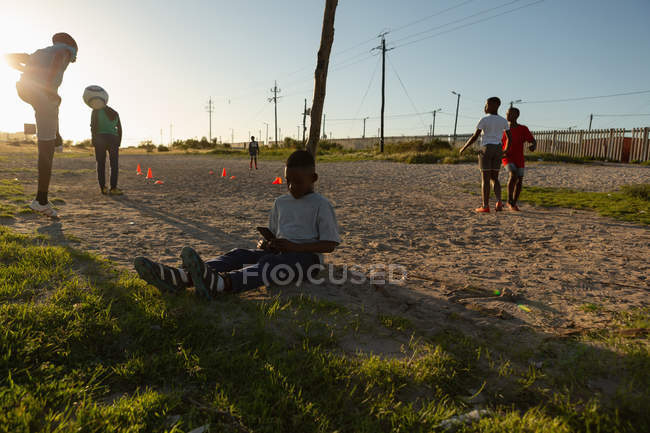 Kid using mobile phone in the ground on a sunny day — Stock Photo