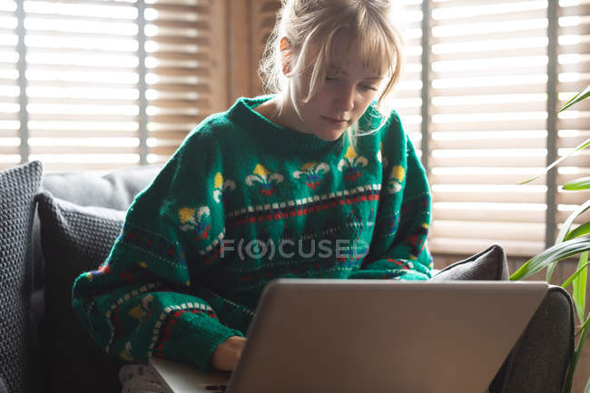 Beautiful woman using laptop in living room at home — Stock Photo