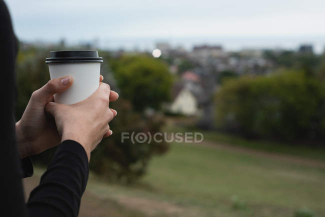 Sección media de la mujer sosteniendo la taza de café en una colina - foto de stock