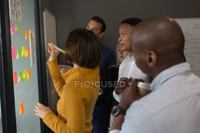 Female executive writing on glass wall in office — Stock Photo