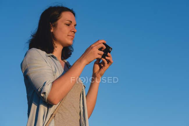 Mulher bonita revendo fotos na câmera — Fotografia de Stock